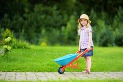 Förtjusande liten flicka som har gyckel med en leksakskottkärra Arkivfoton