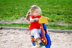 Förtjusande liten flicka som har gyckel på en lekplats utomhus i sommar Royaltyfri Bild