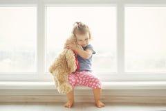Förtjusande liten flicka som kramar en nallebjörn Gulligt behandla som ett barn i vitt rum sitter hemma nära fönster Arkivfoto