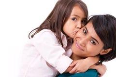 Förtjusande liten flicka som kysser hennes moders kind arkivfoto