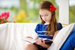 Förtjusande liten flicka som läser en bok i vit vardagsrum på härlig sommardag Fotografering för Bildbyråer