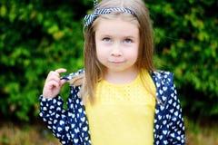 Förtjusande liten flicka som ler i en parkera Arkivfoto