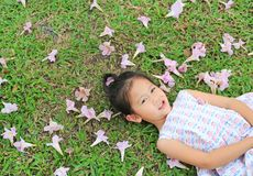 Förtjusande liten flicka som ligger på grönt gräs med den rosa blomman för nedgång i den utomhus- trädgården arkivbilder
