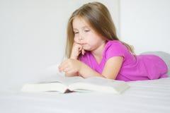 Förtjusande liten flicka som ligger på sängen och läsningen en bok Arkivfoto