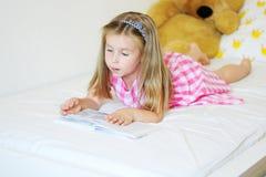 Förtjusande liten flicka som ligger på sängen och läsningen en bok Royaltyfri Fotografi