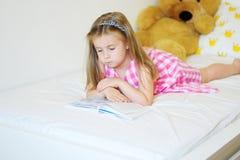 Förtjusande liten flicka som ligger på sängen och läsningen en bok Arkivbild