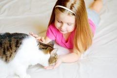 Förtjusande liten flicka som matar hennes katt Arkivfoto