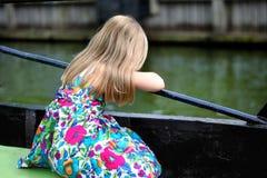 Förtjusande liten flicka som ser floden på en härlig sommardag Arkivbilder