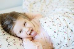 Förtjusande liten flicka som sover i en säng Arkivfoto