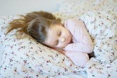 Förtjusande liten flicka som sover i en säng Royaltyfria Bilder