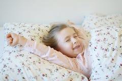 Förtjusande liten flicka som sover i en säng Royaltyfri Fotografi