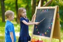 Förtjusande liten flicka som spelar en lärare Arkivfoto