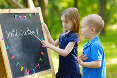 Förtjusande liten flicka som spelar en lärare Royaltyfri Foto
