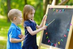 Förtjusande liten flicka som spelar en lärare Arkivbild