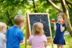 Förtjusande liten flicka som spelar en lärare Arkivbilder