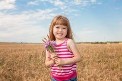 Förtjusande liten flicka som spelar i vetefältet Arkivbild