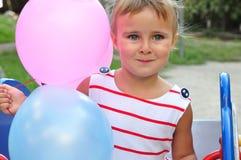 Förtjusande liten flicka som spelar med ballonger royaltyfria bilder