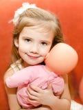 Förtjusande liten flicka som spelar med en docka Arkivbilder