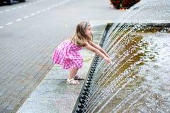 Förtjusande liten flicka som spelar med en stadsspringbrunn på varm och solig sommardag Fotografering för Bildbyråer