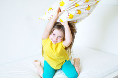 Förtjusande liten flicka som spelar med kudden på sängen i hennes sovrum Royaltyfria Bilder