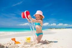 Förtjusande liten flicka som spelar med sand på en perfekt tropisk strand arkivfoton