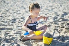 Förtjusande liten flicka som spelar med sand på stranden i sommar Arkivbilder