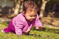 Förtjusande liten flicka som spelar på en parkera Arkivfoto