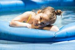Förtjusande liten flicka som spelar på en utomhus- simbassäng Fotografering för Bildbyråer