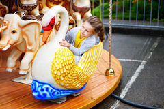Förtjusande liten flicka som spelar på karusell på nöjesfältet Arkivbilder