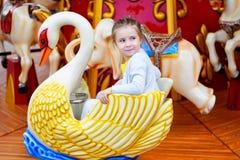 Förtjusande liten flicka som spelar på karusell på nöjesfältet Royaltyfri Bild