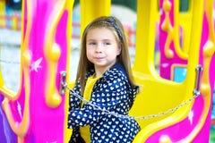 Förtjusande liten flicka som spelar på karusell på nöjesfältet Arkivbild