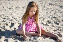 Förtjusande liten flicka som spelar på stranden Arkivbilder
