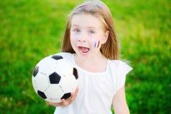 Förtjusande liten flicka som stöttar hennes nationella fotbollslag under fotbollmästerskap Royaltyfri Bild
