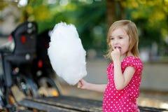 Förtjusande liten flicka som utomhus äter godis-floss royaltyfri fotografi