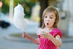Förtjusande liten flicka som utomhus äter godis-floss royaltyfri bild