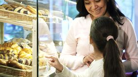 Förtjusande liten flicka som väljer bakelse i ställa ut, medan shoppa med hennes moder arkivfoto