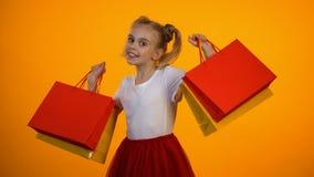 Förtjusande liten flicka som visar shoppingpåsar, rabatter och försäljningar, svarta fredag stock video