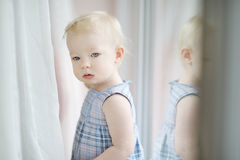 Förtjusande liten flicka vid fönstret Arkivfoton