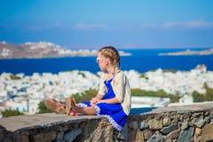Förtjusande liten flickabakgrundsMykonos stad i Europa Arkivbilder
