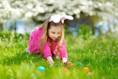 Förtjusande liten flickajakt för det easter ägget på påskdag Arkivbilder