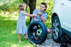 Förtjusande liten flickaportionfader som utomhus ändrar ett bilhjul på härlig sommardag arkivbild