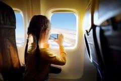 Förtjusande liten flickaresande vid ett flygplan Arkivbilder