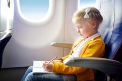 Förtjusande liten flickaresande vid ett flygplan Barnsammanträde vid den flygplanfönstret och teckningen en bild med färgrika bly Fotografering för Bildbyråer