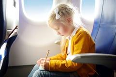 Förtjusande liten flickaresande vid ett flygplan Barnsammanträde vid den flygplanfönstret och teckningen en bild med färgrika bly Royaltyfria Bilder