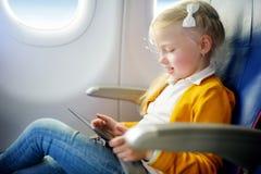 Förtjusande liten flickaresande vid ett flygplan Barnsammanträde vid den flygplanfönstret och teckningen en bild med färgrika bly Arkivbilder