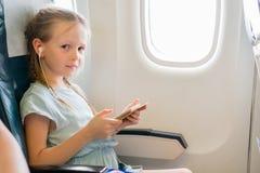 Förtjusande liten flickaresande vid ett flygplan Gullig unge med bärbara datorn nära fönster i flygplan Arkivbild