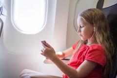 Förtjusande liten flickaresande vid ett flygplan Lyssnande musik för unge som sitter nära flygplanfönster Arkivfoton