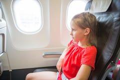 Förtjusande liten flickaresande vid ett flygplan Unge som sitter nära flygplanfönster Royaltyfria Bilder