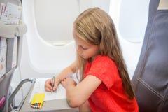 Förtjusande liten flickaresande vid ett flygplan Ungeteckningsbild med färgrika blyertspennor som sitter nära fönster Arkivfoto