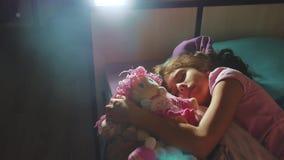Förtjusande liten flickasömn i soffasängen och att krama henne för att behandla som ett barn - dockan liten brunettflicka som in  arkivfilmer